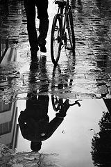 Polkupyöräntaluttaja heijastuu lätäköstä (mustavalkoinen)