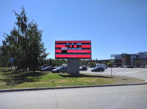 """Videra-merkkinen digitaalinen mainostaulu Linnanmaan Prisman parkkipaikan edustalla. Näytössä Valkean mainos: """"ALE"""", """"Kauppakeskus täynnä tarjouksia!"""" Näytön vasemmalla puoliskolla suorakaiteen muotoinen alue täynnä satunnaisia pikseleitä, sen alla saman kokoinen musta suorakaide."""