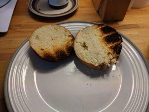 Halkaistu hampurilaissämpylä lautasella, molemmat puoliksi palaneita
