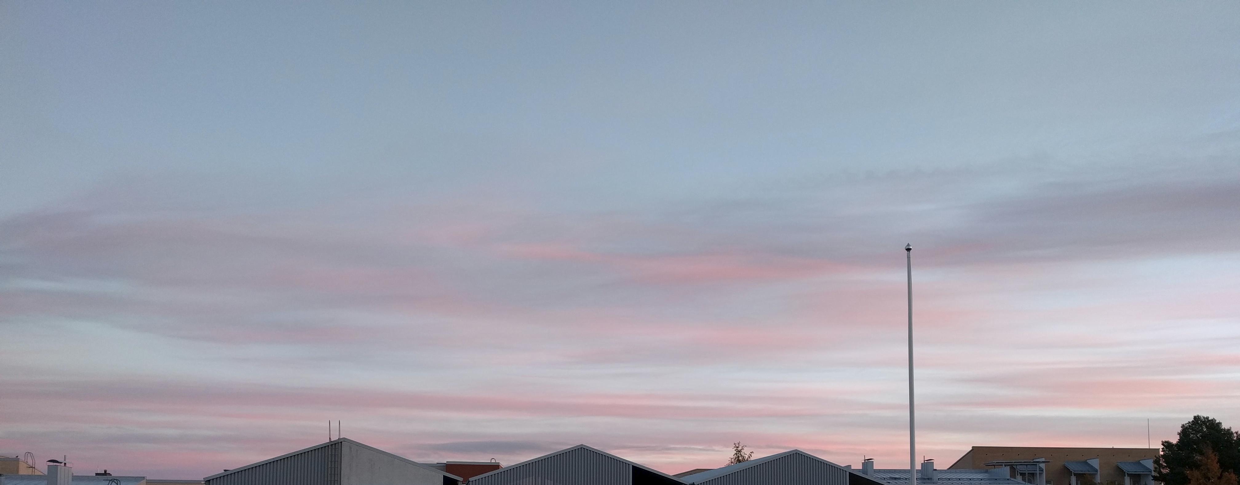 Aamuruskon vaaleanpunaisia pilviä kattojen yllä