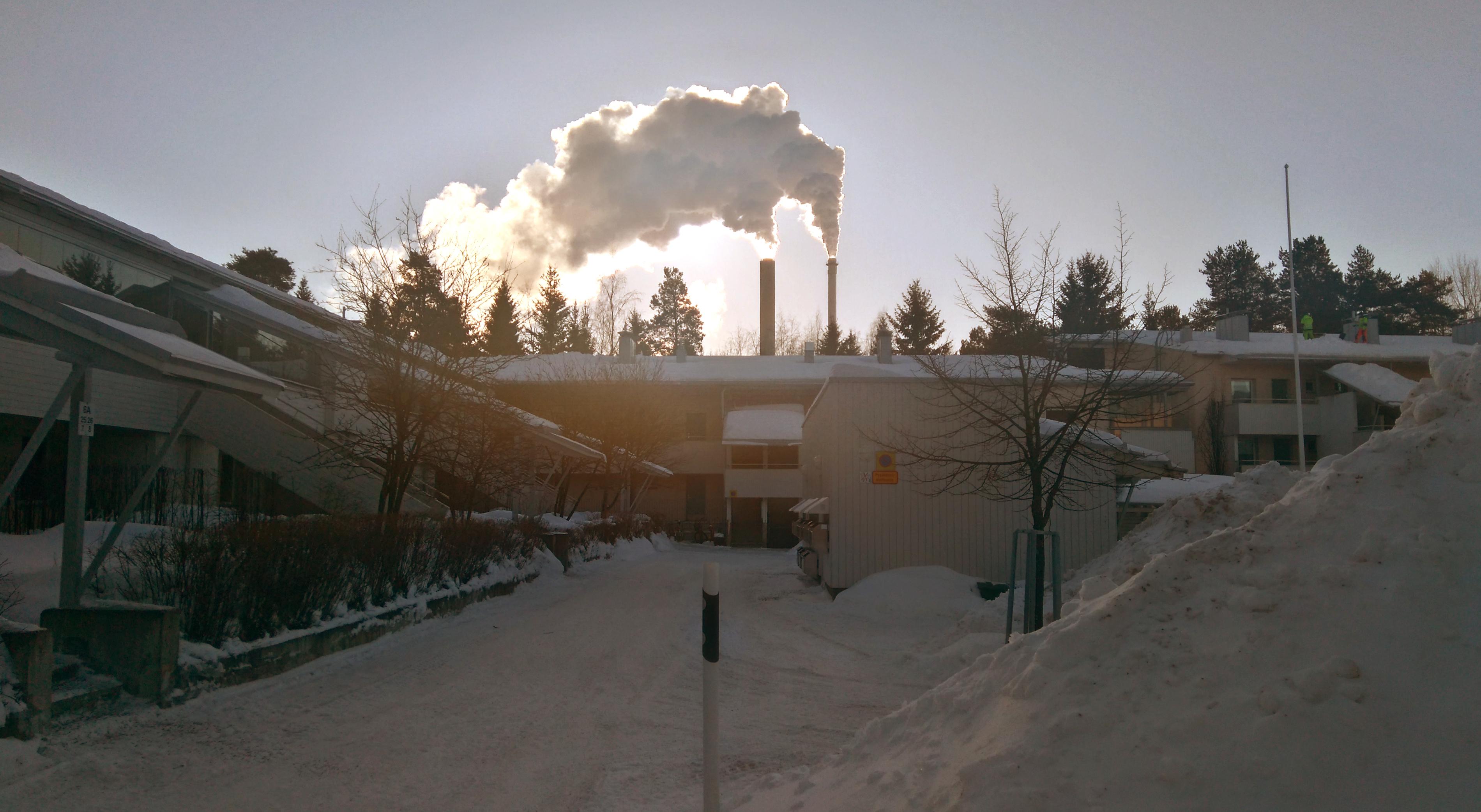 Aurinko paistaa voimalan piipuista nousevan savun takana