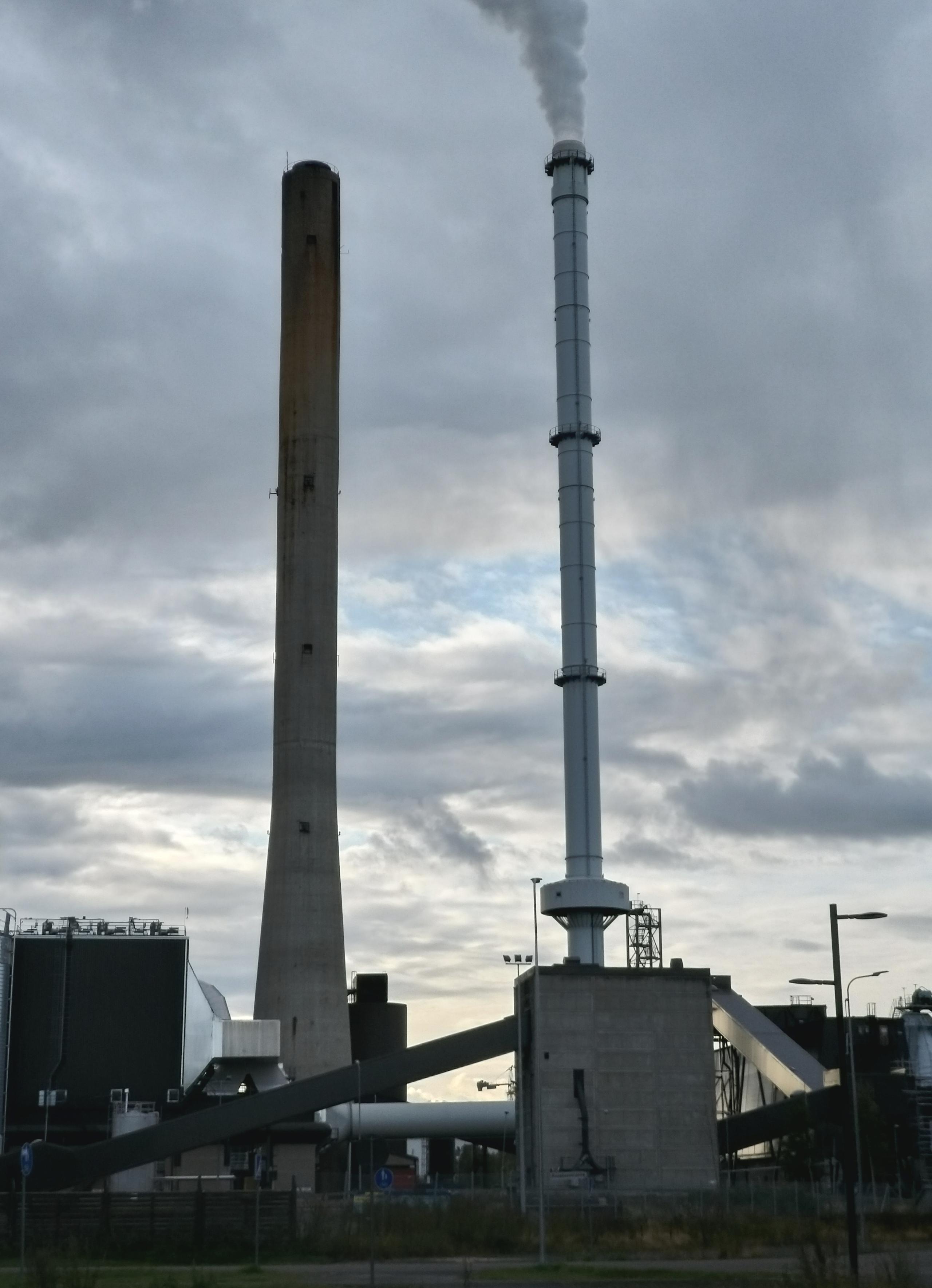 Toppilan voimalaitoksen (Toppila 1) piiput maantasolta kuvattuina, taustalla pilviä
