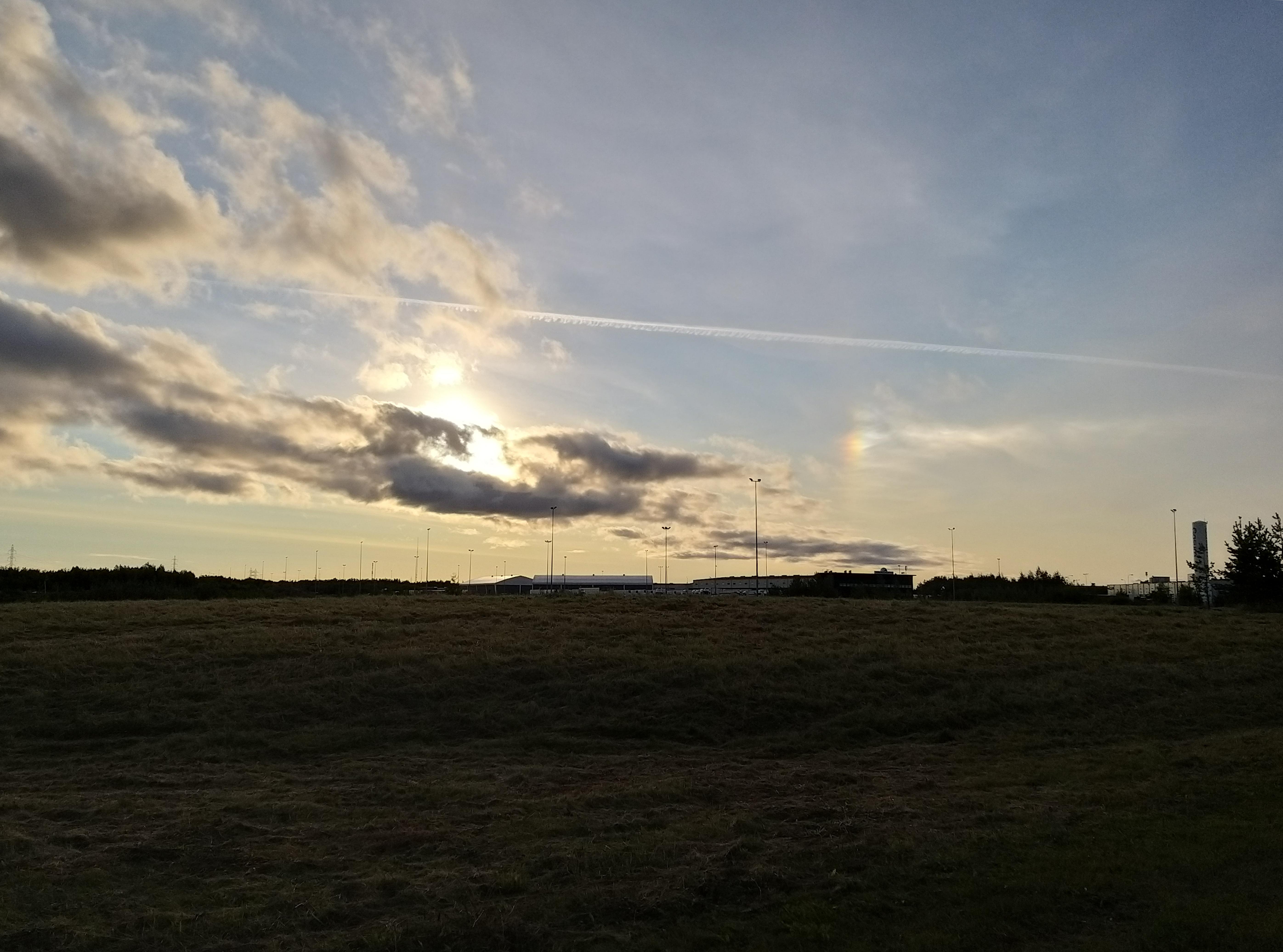 Aurinko pilvien takana, hallimaiseman yllä. Auringosta oikealle puna- ja sinisävyinen sivuaurinko.