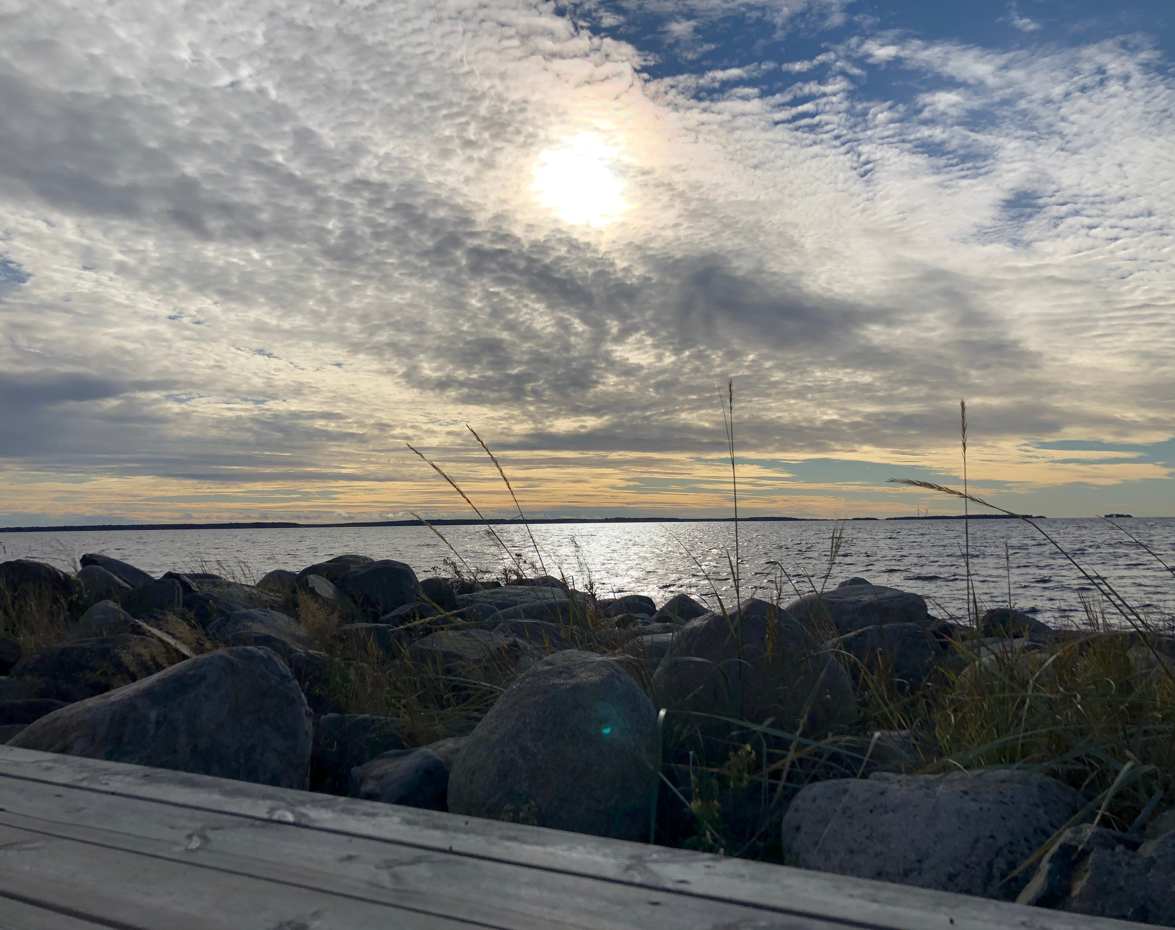 Merihorisonttinäkymä. Taivaalla aurinko kuultaa läpi harmaanvalkean, ohuen hattarapilven. Taivaarannassa saaria; oikealla saari, jolla kaksi tuuliturbiinia. Auringonvalo heijastuu merenpinnasta; pinnalla myös pientä veden aaltoilua. Etualalla (rannassa) harmaita kivenlohkareita ja niiden väleissä kasvavia heinänkorsia, joiden ylimmät kukinnot yltävät kuvassa lähes auringon korkeudelle. Keskimmäisen kiven päällä turkoosi, puolikuun muotoinen linssiheijastuma auringosta. Alimpana kuvassa (aivan etualalla) puinen, harmaista lankuista tehty terassi.